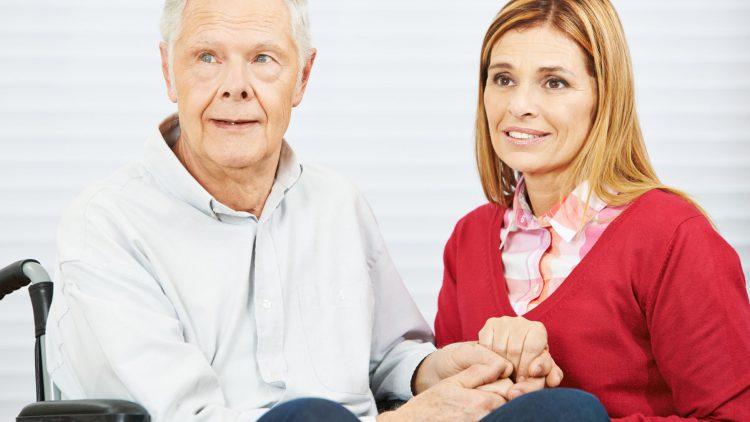 Entscheidung häusliche Pflege - Senior im Rollstuhl und erwachsene Tochter halten Hände