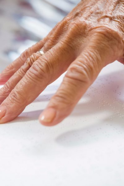 Mit den Händen lesen - Ältere Frau liest ein in Blindenschrift verfasstes Buch