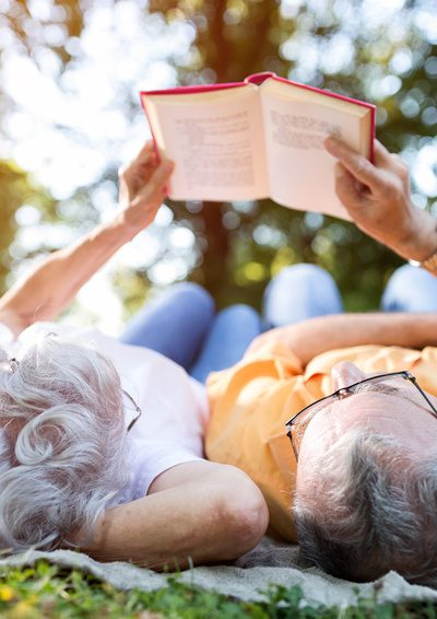 Bücher machen nicht nur schlau, sondern halten auch geistig rege - Älteres paar gemeinsam auf der Wiese liegend und lesend