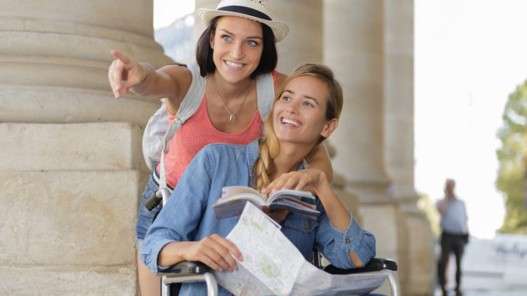 Reiseveranstalter für Menschen mit Behinderung - Rollstuhlfahrerin mit Karte in der Hand lässt sich den Weg zeigen