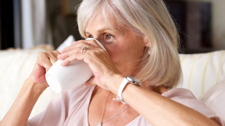 Ältere Frau mit einer Tasse Tee - Wie Sie mit kleinen Ritualen Ihr Wohlbefinden steigern