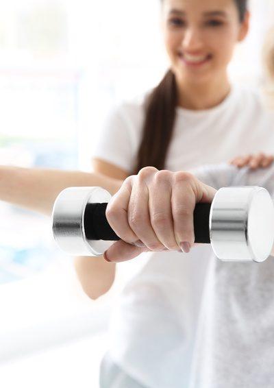 Viel Bewegung und die richtige Ernährung können Osteoporose aufhalten - Frau mit Hanteln beim Sport