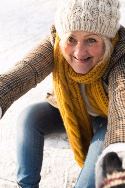 Keine Angst vor Stürzen in der kalten Jahreszeit - Ältere Frau lässt sich nach einem Sturz auf dem Eis aufhelfen