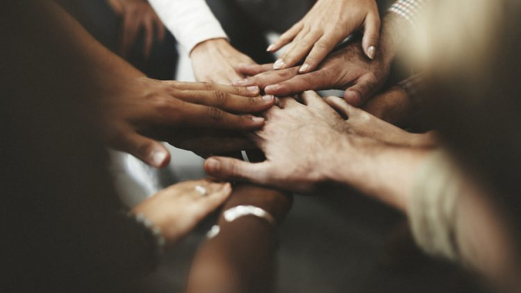 Freiwillige sind aktive Überzeugungstäter - Menschen legen die Hände aufeinander