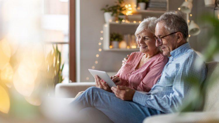 Oma und Opa sitzen auf der Couch und schauen sich Bilder an