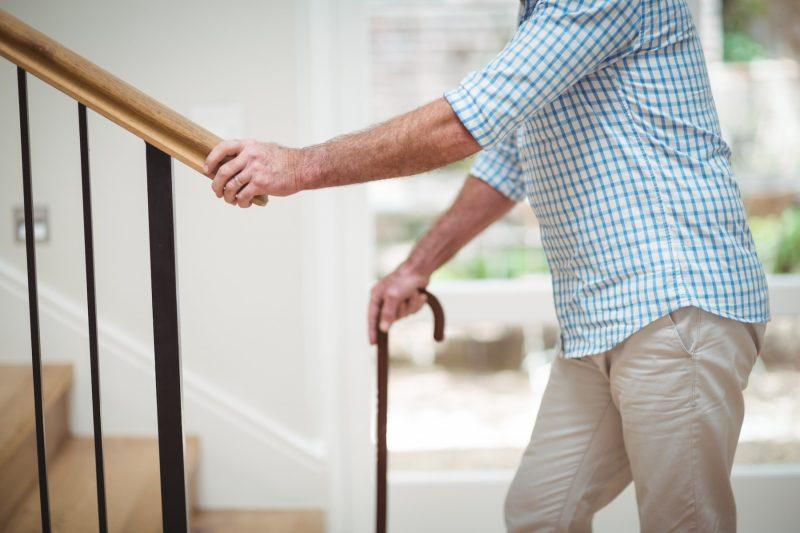 Opa lehnt sich an Treppengeländer