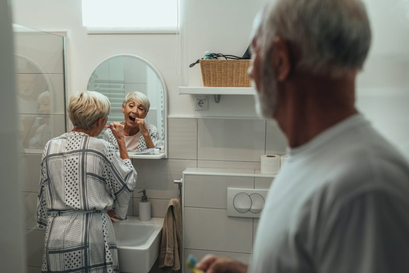 Oma nutzt Zahnseide vor dem Spiegel