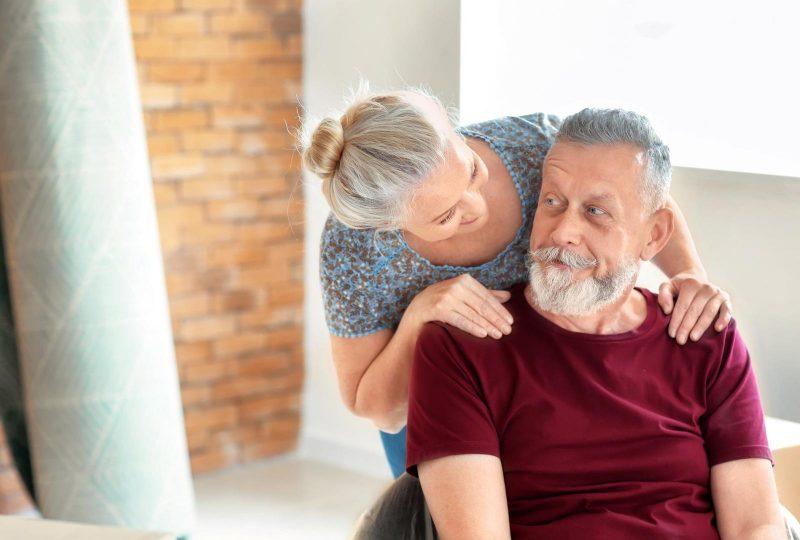 Optimaler Wohnraum - Frau legt Mann Hände auf die Schulter und schaut ihn an