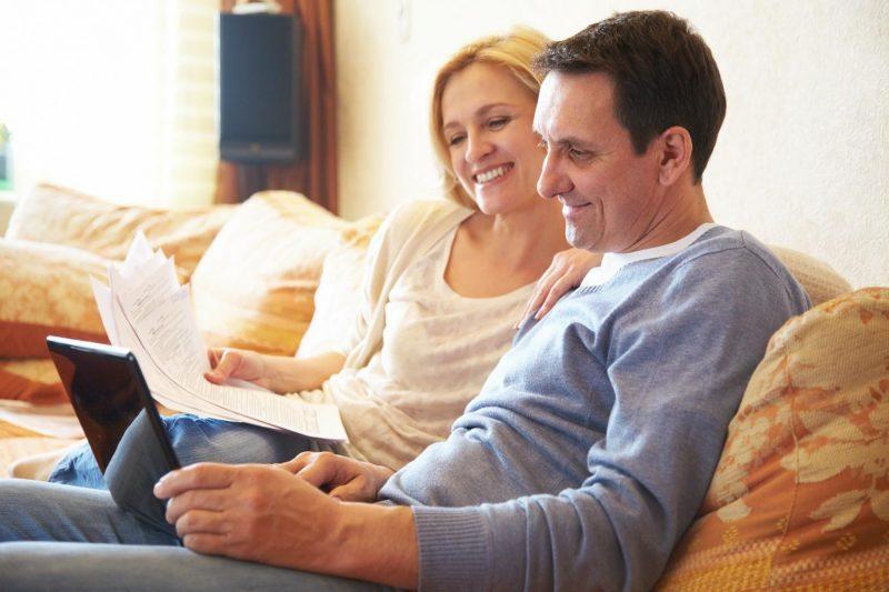 Optimaler Wohnraum - Mann und Frau sitzen auf der Couch am Laptop