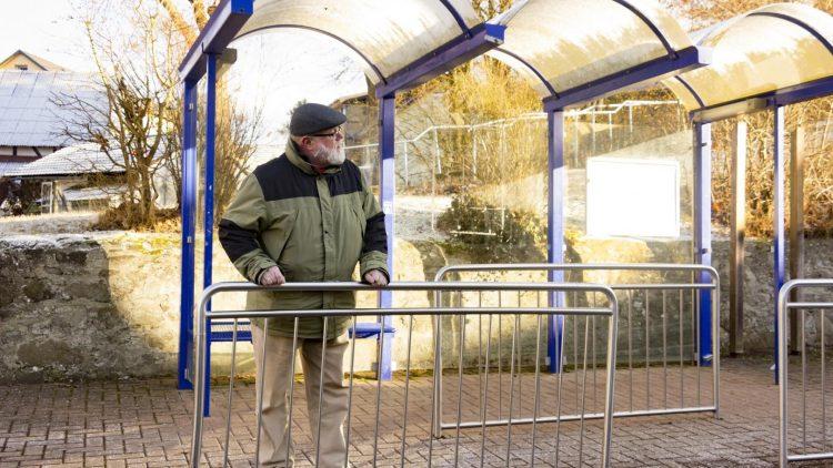 Alter Mann steht an Absperrung an Bushaltestelle