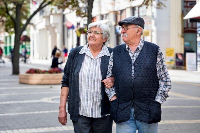 Opa und Oma gehen Arm in Arm durch die Stadt