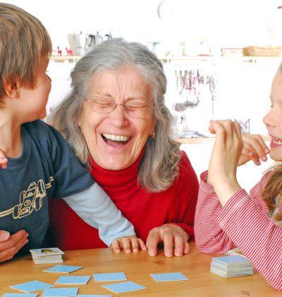 Gehirnjogging - Großmutter sitzt mit Enkelkindern in der Küche beim Memory