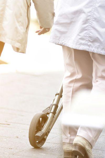 Bewegungsmangel erhöht die Sturzgefahr - Frau mit Rollator in Belgeitung eines Mannes