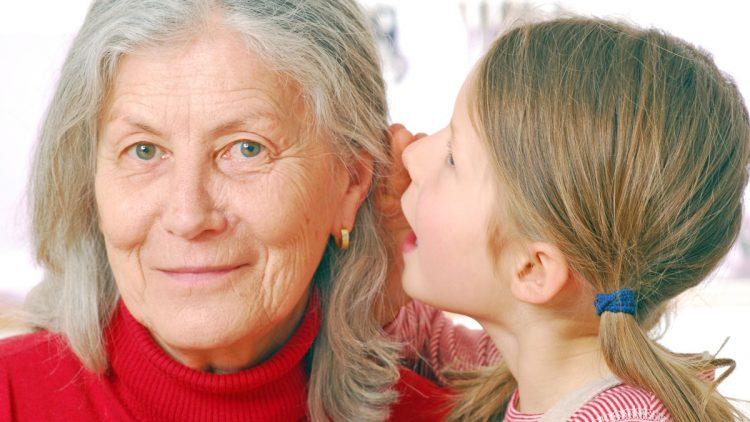 Altersschwerhoerigkeit erkennen und behandeln - Enkelin flüster ihrer Großmutter ins Ohr