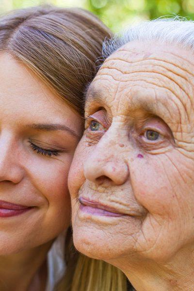 7 Warnzeichen für eine Erkrankung - Enkelin umarmt ihre apathische Großmutter