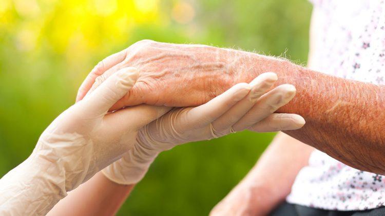 Ambulante Pflege in Zeiten der Corona-Krise - Hände in Schutzhandschuhen halten Hand einer älteren Frau