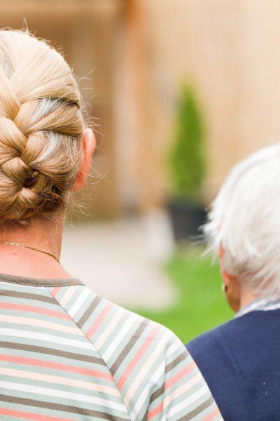 Beratung für pflegende Angehörige - Greise Mutter und Tochter mittleren Alters Arm in Arm