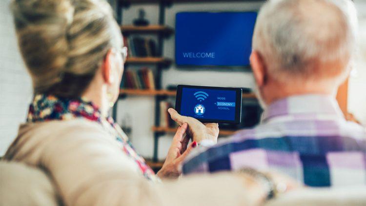 Ehepaar mit smarter Steuerung der Haustechnik in den Händen