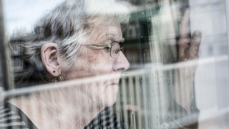 Einsamkeit und soziale Isolation - Ältere Frau blickt traurig aus dem Fenster