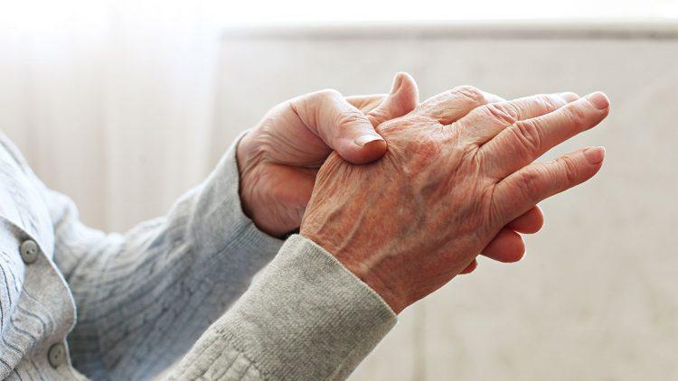 Die richtige Ernährung bei rheumatoider Arthritis - Ältere Frau knetet schmerzene Hände