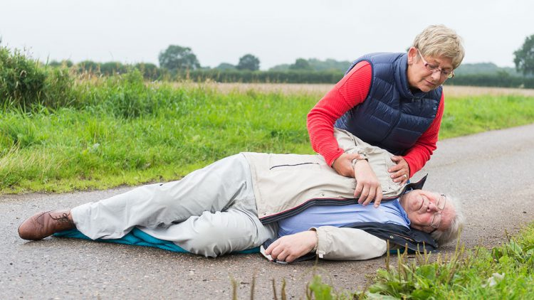 Wie Sie im Notfall einenkühlen Kopf bewahren - Ältere Frau kniet über einem bewusstlos liegenden älteren Mann