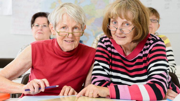 Zwei ältere Damen im Klassenraum mit den Fingern auf der Landkarte