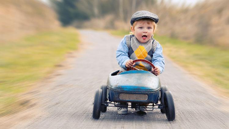 Fahrtauglichkeit im Alter - Kleines Kind mit nostalgischem Tretauto unterwegs