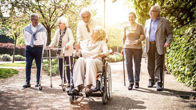 Senioren beim Spaziergang mit Rollstuhl, Gehstock und Rollator