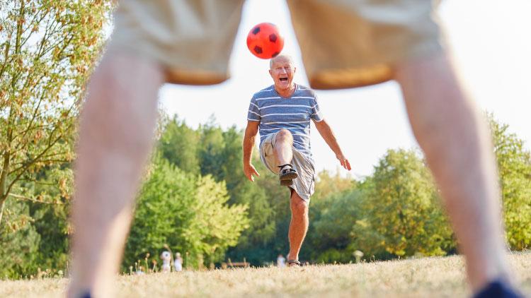 Von wegen Seniorensport - Älterer agiler Mann auf einer Wiese beim Kicken eines Fußballs