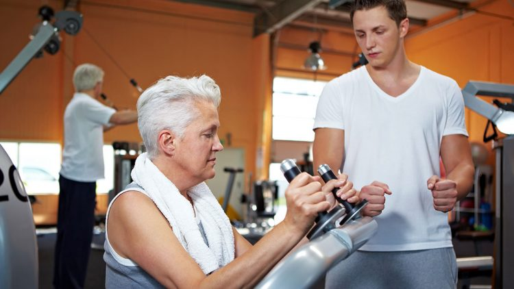Seniorin lässt sich von jungem Trainer die Bedienung eines Fitnessgerätes erklären