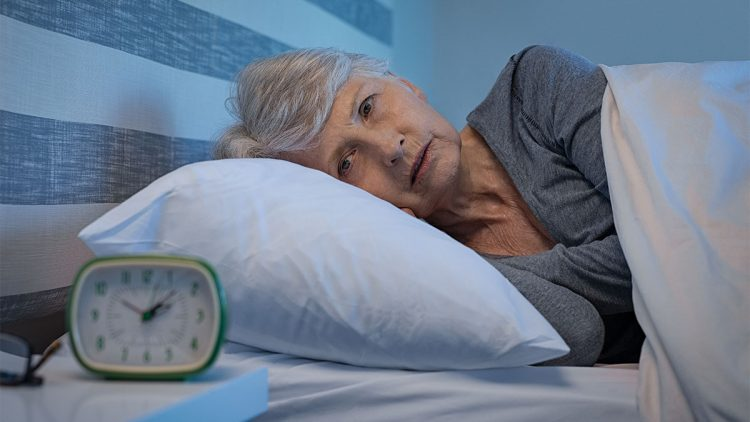 Schlaflos in der Nacht - Frau im Bett schaut auf den Wecker