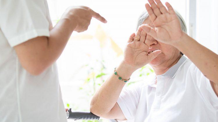 Gewalt in der Pflege - Pflegekraft mit aggressiver Geste gegenüber abwehrender Seniorin