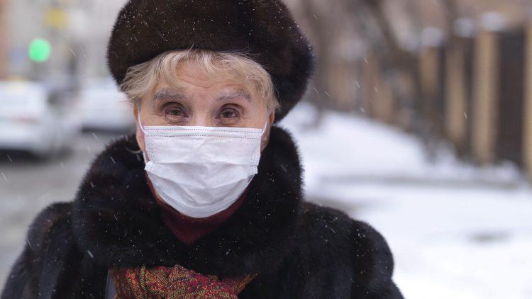 Effektiver Grippeschutz - Ältere Dame mit Pelz und Mundschutz bei Schnee