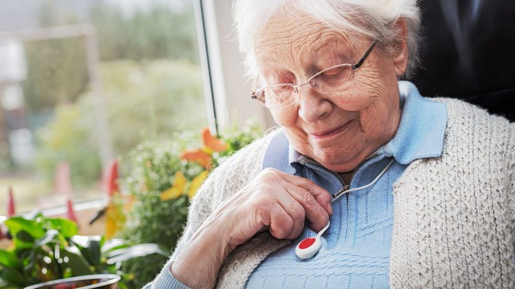 Was ein Hausnotruf leisten muss - Seniorin mit Notfallknopf um den Hals