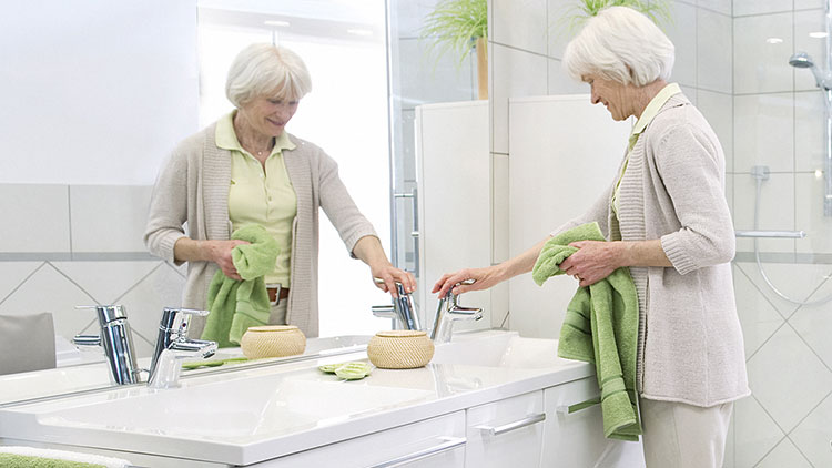 Jedes Händewaschen zählt - Ältere Frau mit Handtuch am Waschbecken