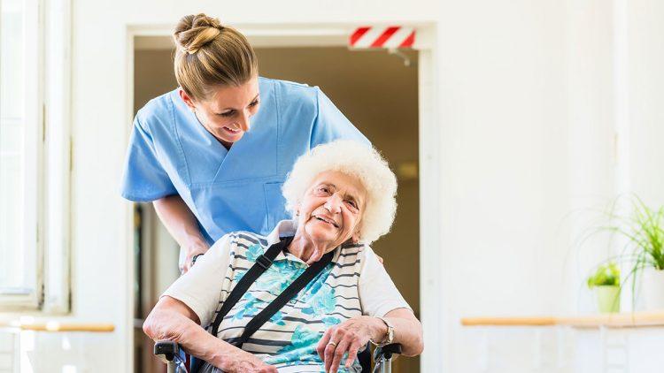 Kurzzeitpflege - Pflege auf Zeit - Pflegekraft schiebt Seniorin im Rollstuhl