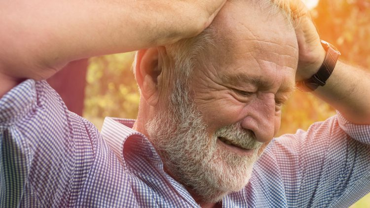 Leben als umgeschulter Linkshänder - Älterer Mann hält sich mit beiden Händen den Kopf
