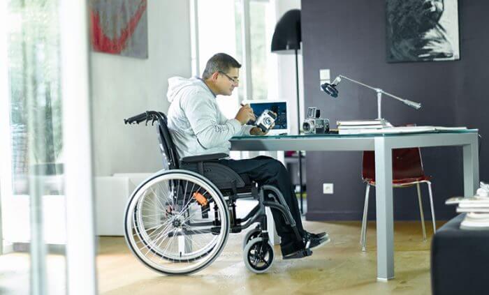 Barrierefreies Wohnen - Rollstuhlfahrer am Tisch beim Aufschrauben einer alten Kamera