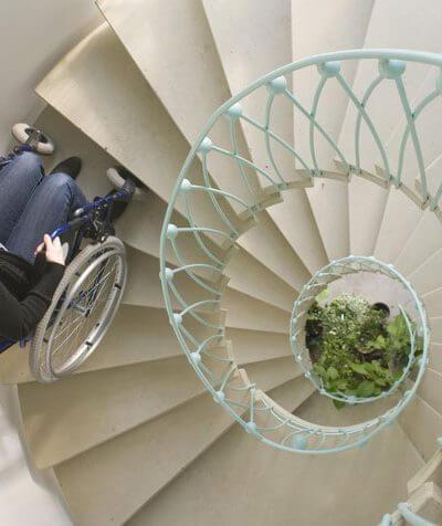 Barrierefreies Wohnen - Rollstuhlfahrerin auf einer Wendeltreppe