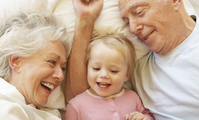 Barrierefreies Wohnen - Großeltern mit Enkeltochter beim Kuscheln im Bett