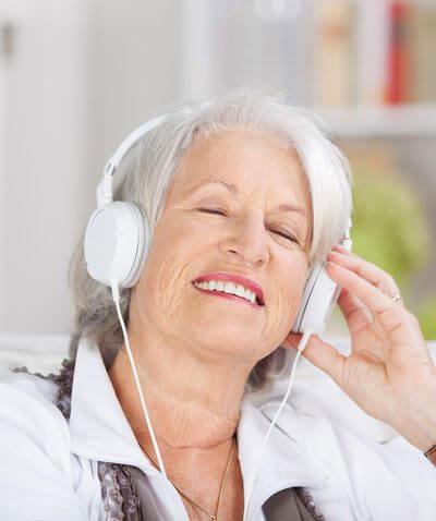 Stolperfalle Wohnzimmer - Frau mit Kopfhörern auf der Couch