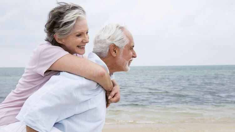 Für ein aktives und selbstbestimmtes Leben - Mann mit Frau Huckpack am Meer