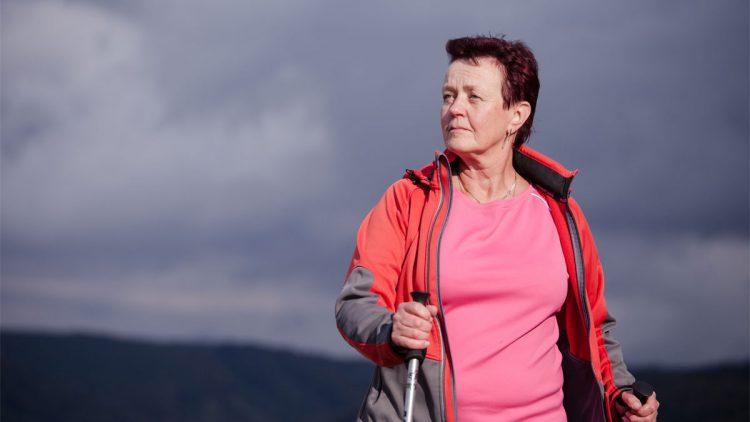 Frau mit Nordic-Walking-Stöcken vor grauem Gewitterhimmel