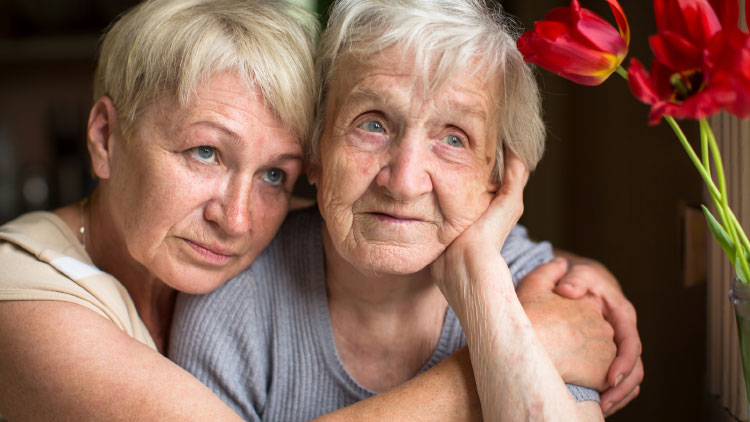 Pflege mit Herz - Ältere Frau umarmt von ihrer Tochter beim Blick aus dem Fenster