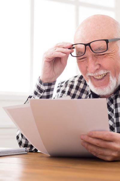 Pflegekostenzuschuss beantragen - Älterer Mann schaut lächelnd auf seinen Antrag