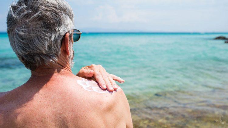 Was Sie zur Vorbeugung einer Krebserkrankung tun können - Älterer Mann beim Auftragen von UV-Schutz auf die Haut