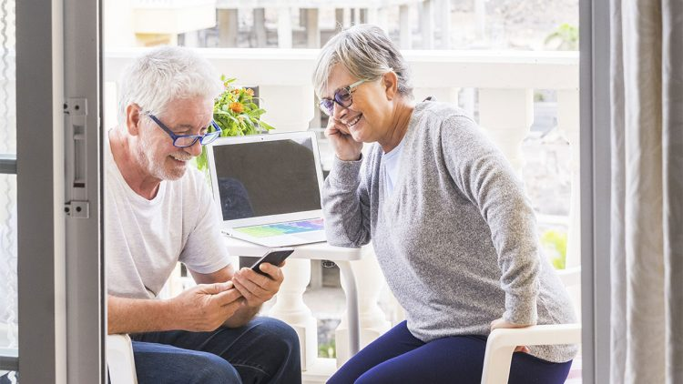 Reisebuchung - Älterer Mann und Frau sitzen auf dem Balkon mit Notebook und Handy