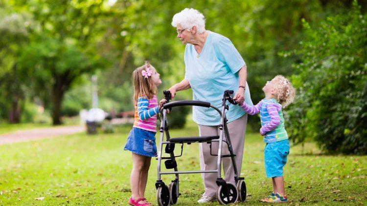 Viele Unfälle mit den Gehhilfen wären vermeidbar | Großmutter mit Rollator auf der Wiese mit Enkelkindern
