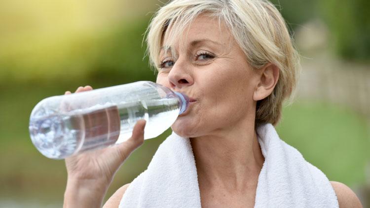 Gesund leben beginnt im Kopf - Frau mittleren Alters beim Trinken von Wasser nach dem Sport