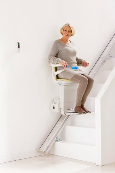SANIMED 10 plus Treppenlifter für gerade Treppen Person fährt mit Lift in einem weißen Treppenhaus, elegant!